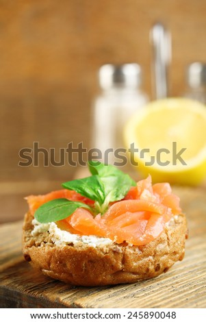 Canape with salmon and herbs on wooden background