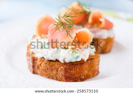 Canape with smoked salmon and cream cheese on plate, selective focus, low angle view - stock photo