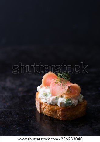 Canape with smoked wild salmon and cream cheese, dark background, selective focus, copy space - stock photo