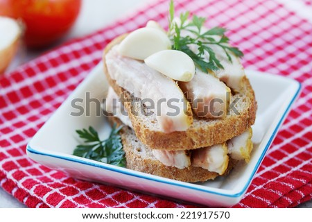 Canapes of Ukrainian lard with garlic and herbs - stock photo