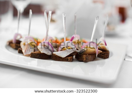 canapes on a white plate on the table - stock photo