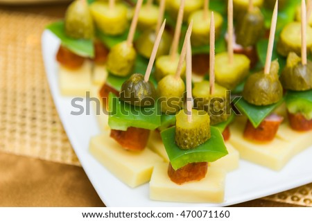 Canapes on toothpicks. Plate of appetizers for party.