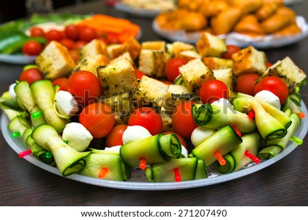 Canapes sandwiches of mozzarella cheese, tomato, cucumbers and bread - stock photo