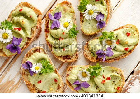 Canapes with avocado paste and edible flowers - stock photo