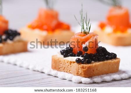 Canapes with black sturgeon caviar, smoked salmon and dill. macro. horizontal  - stock photo