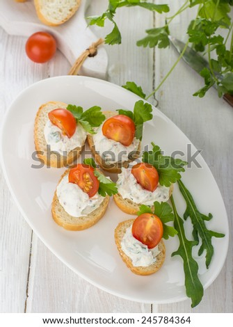 canapes with cheese and venetables on a light background with arugula and cilantro. Selective focus - stock photo