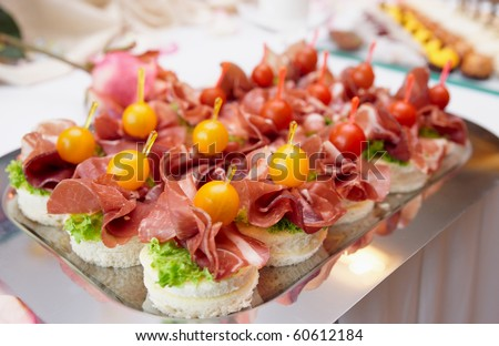 Canapes with cured ham (jamon or prosciutto) on banquet table - stock photo