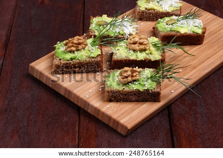 Canapes with paste of avocado, walnuts, cheese and sesame seeds. Snack of canapes with avocado, nuts and herbs on a kitchen board. The concept of the restaurant, a healthy diet food, holiday food. - stock photo