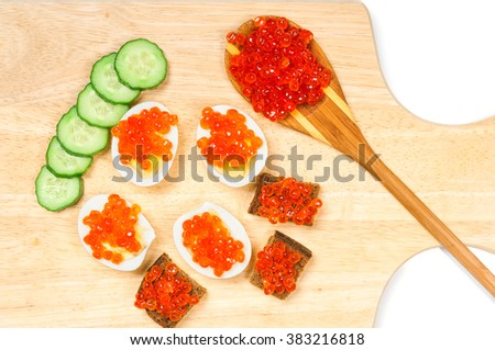 Canapes with red caviar and cucumbers on wooden board - stock photo