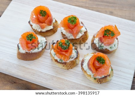 canapes with salmon and cheese on wooden board