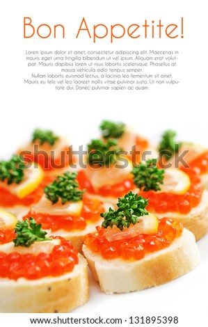 Canapes with salmon caviar, lemon and parsley on plate - stock photo