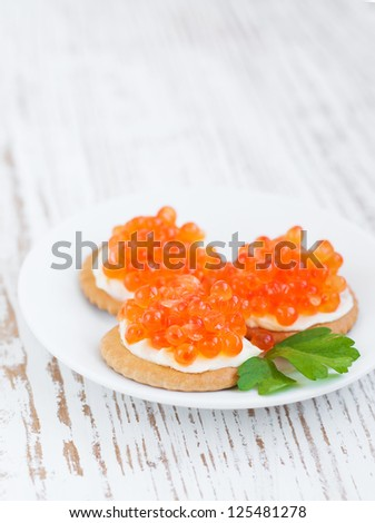 Canapes with  salmon red caviar on a wooden background