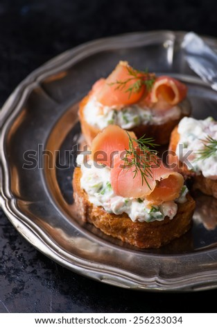 Canapes with smoked salmon and cream cheese on vintage metal plate, selective focus - stock photo