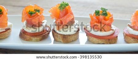 canapes with smoked salmon on wooden board