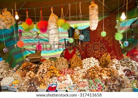 CANAR, ECUADOR - JUNE 19, 2010: Unknown indigenous woman selling traditional ecuadorian sweets - stock photo