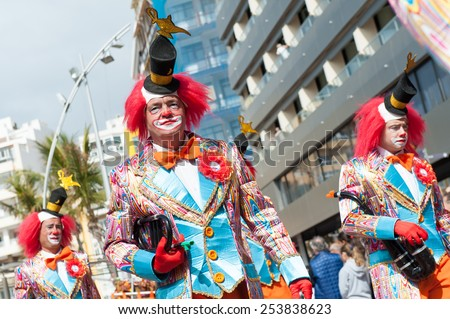 CANARY ISLAND, SPAIN - FEBRUARY 17, 2015: Unidentified men with clown costumes from Murga Los nietos de Kika walking to samba rhythms in the streets during city of Las Palmas carnival in the sun.