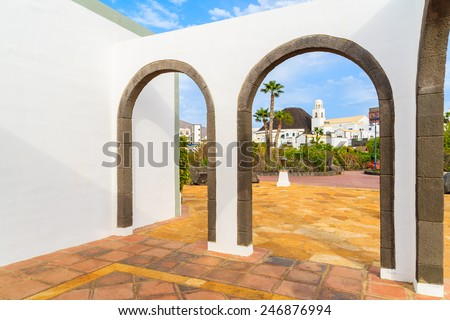 Canary style building with view of buildings in marina Rubicon thorough arches, Lanzarote, Canary Islands, Spain  - stock photo