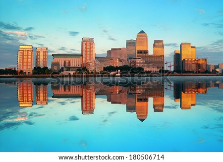 Canary Wharf business district in London at sunset with reflection.  - stock photo
