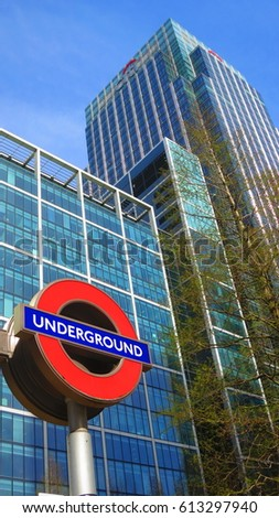 Canary Wharf, London - 30 March, 2016: Iconic London Underground symbol for the Canary Wharf subway station in the Isle of Dogs, Canary Wharf with colorful background on sunny clear day. 30/03/2016