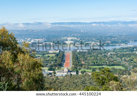 Canberra view from Mount Ainslie over orange coloured Anzac Parade below to Houses of Parliament and Molonglo River
