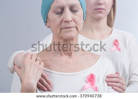 Cancer woman and young girl with pink ribbon, embracing  - stock photo