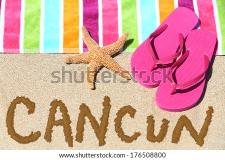 Cancun, Mexico beach travel concept. CANCUN written in sand with water next to beach towel, summer sandals and starfish. Summer and sun vacation holidays. - stock photo