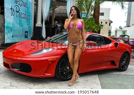 CANCUN, MEXICO - MAY 03: Model Morgan Maria poses outside with red car during semi-finals IBMS 2014 at the Mandala Beach on May 03, 2014 in Cancun, Mexico.