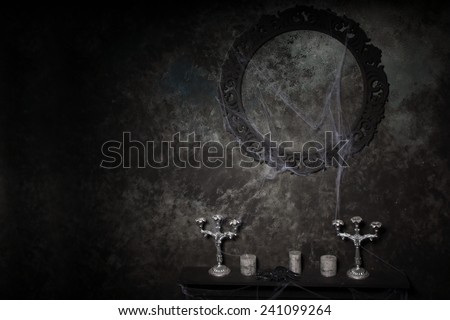 Candelabras and Empty Ornate Frame Covered in Cobwebs on Table in Eerie Halloween Haunted House Setting - stock photo