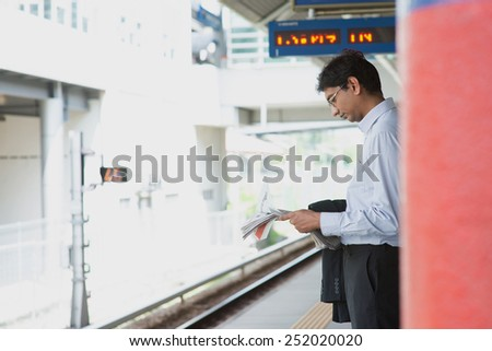 Candid Asian Indian businessman waiting at public train station, standing and reading on newspaper. - stock photo