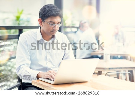 Candid Asian Indian man using laptop computer at outdoor cafe. - stock photo