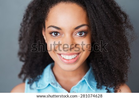 Candid beauty. Portrait of attractive young African woman looking at camera and smiling while standing against grey background  - stock photo