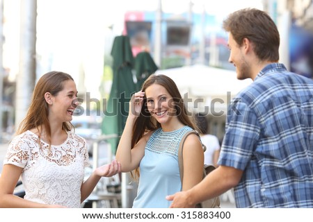 Candid girl with a friend flirting with a boy in the street - stock photo