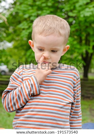 Candid image of a thoughtful little boy standing picking his nose outdoors in a garden or park - stock photo