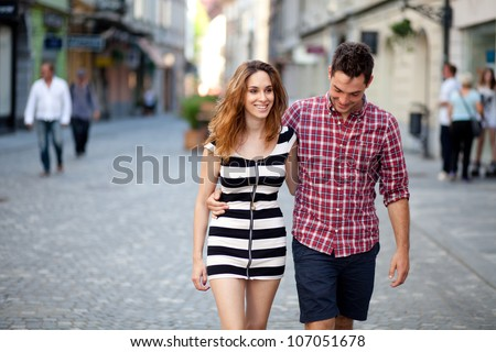 Candid image of a young couple walking in the old part of town - stock photo