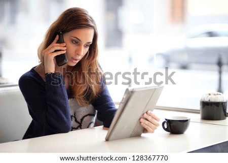 Candid image of a young woman talking on the phone in a cafe. Selective focus. - stock photo