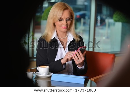 Candid photo of a attractive middle-aged blond businesswoman working at hotel lobby with a tablet pc and drinking coffee - stock photo