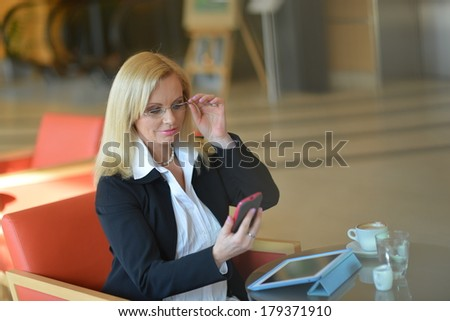 Candid photo of a attractive middle-aged blond businesswoman working at hotel lobby with a tablet pc/smartphone and drinking coffe - stock photo