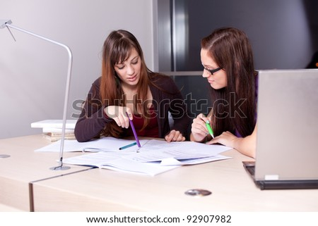 Candid photo of a couple of students studying together - stock photo