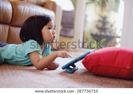 Candid picture of baby girl playing games on tablet  - stock photo