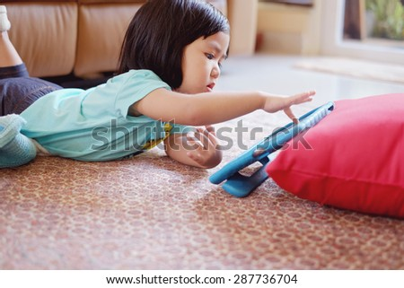 Candid picture of baby girl playing on tablet