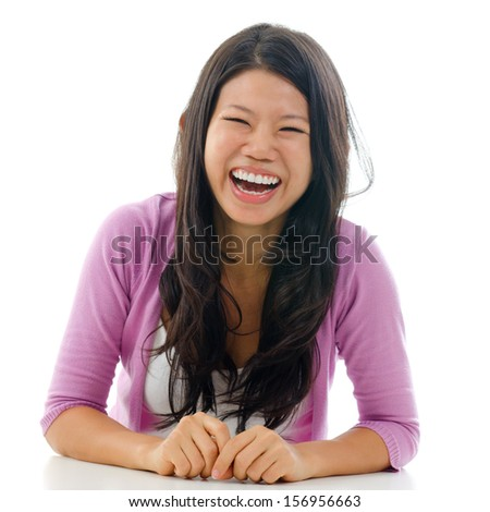 Candid portrait Asian woman laughing with mouth opened big. Sitting isolated on white background.