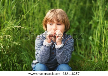 Candid portrait of adorable little boy of 4-5 years old, wearing blue hoody, playing alone outdoors
