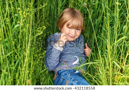 Candid portrait of adorable little boy of 4-5 years old, wearing blue hoody, playing alone outdoors, laying on grass - stock photo