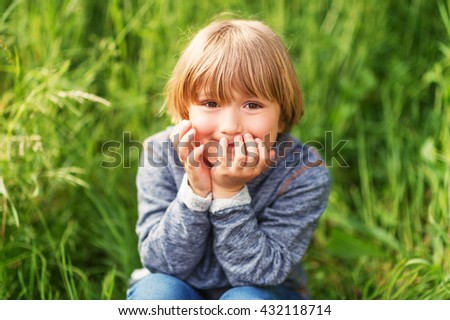 Candid portrait of adorable little boy of 4-5 years old, wearing blue hoody, playing alone outdoors - stock photo