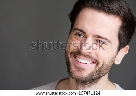 Candid portrait of an attractive young man smiling on gray background - stock photo