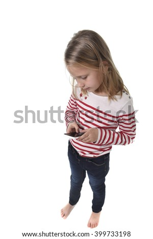 candid portrait of beautiful female child with blond hair and blue eyes using mobile phone playing game excited isolated on white background in children internet gaming addiction concept