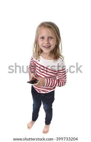 candid portrait of beautiful female child with blond hair and blue eyes using mobile phone playing game excited isolated on white background in children internet gaming addiction concept - stock photo