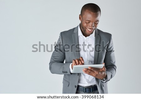 Candid portrait of positive friendly black  professional businessman with touchscreen tablet device isolated in studio
