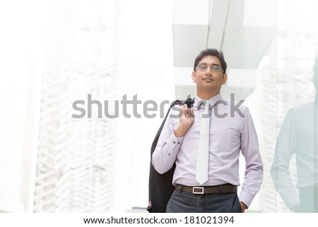 Candid portrait of 30s Asian Indian businessman walking outside office. India male business man, real modern office building as background with natural sunlight. - stock photo