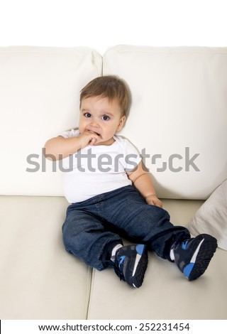 candid portrait of sweet happy little baby boy lying alone on sofa couch at home wearing small jeans and sneakers in growth concept
